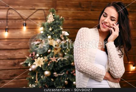 Smiling woman near Christmas tree making phone call stock photo, Smiling woman near Christmas tree making phone call in living room by mykhalets