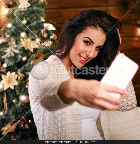 people, holidays and technology concept - beautiful brunette woman in white  sweater taking selfie picture by smartphone over christmas tree and living room background stock photo, people, holidays and technology concept - beautiful brunette woman in white Christmas sweater taking selfie picture by smartphone over christmas tree living room background by mykhalets