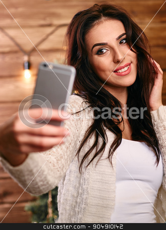 Portrait of a beautiful brunette taking a selfie with her smart phone at home stock photo, Portrait of a beautiful brunette taking a selfie with her smart phone   by mykhalets