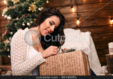 happy young woman opening christmas gift near christmas tree stock photo, happy young woman  opening christmas gift near christmas tree by mykhalets