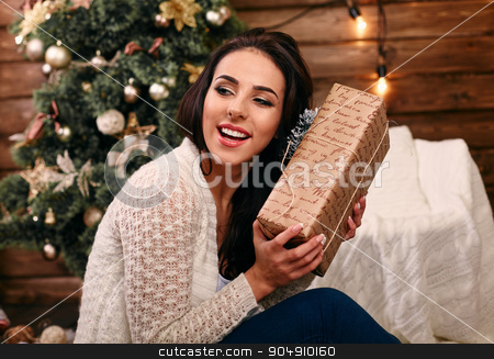 Excited young woman with christmas present box in front of christmas tree stock photo, Excited young woman with christmas present box in front of christmas  tree  by mykhalets