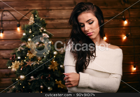 Beautiful young woman  near christmas tree stock photo, Beautiful young woman with present near christmas tree by mykhalets