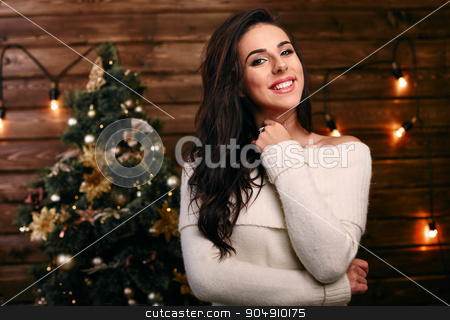 Indoor lifestyle portrait of pretty smiling girl with bright make up and amazing brunette long hairs  Posing near New Year tree and fireplace. Surprised emotions. stock photo, Christmas Santa hat isolated woman portrait . Smiling happy girl on white background. by mykhalets