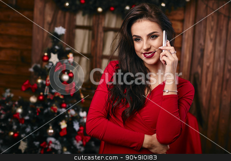 Young woman in red dress  talking on mobile phone at Christmas decorated home stock photo, Young woman in red dress  talking on mobile phone at Christmas decorated home. by mykhalets