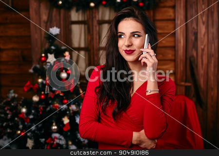 Young woman in red dress  talking on mobile phone at Christmas decorated home stock photo, Young woman in red dress  talking on mobile phone at Christmas decorated  home by mykhalets