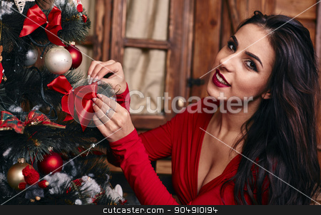 Portrait of attractive caucasian woman brunette, studio shot in red dress putting a christmas balls in christmas tree stock photo, Portrait of attractive caucasian woman blond, studio shot in red dress putting a   balls in christmas tree by mykhalets