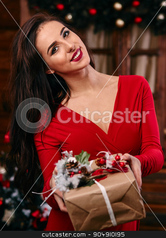indoor portrait of elegant woman with make-up and hair-style posing near decorated Christmas tree with gift box in the hand stock photo, indoor portrait of elegant woman with make-up and hair-style posing near decorated  Christmas tree with gift box in the hand by mykhalets