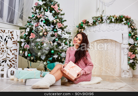 Young woman near a Christmas tree holding gift box while sitting  stock photo, Young beauty smiling santa woman near the Christmas tree. Fashionable luxury girl celebrating New Year. Beautiful luxury trendy brunette by mykhalets