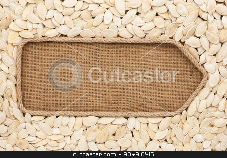 Pointer made from rope with pumpkin seeds  lying on sackcloth stock photo, Pointer made from rope with pumpkin seeds  lying on sackcloth, with space for your text by alekleks