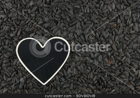 Heart pointer, the price tag lies on sunflower seeds stock photo, Heart pointer, the price tag lies on sunflower seeds,  with space for your text by alekleks