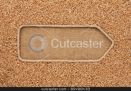 Pointer made from rope with grain wheat  lying on sackcloth stock photo, Pointer made from rope with grain wheat  lying on sackcloth, with space for your text by alekleks