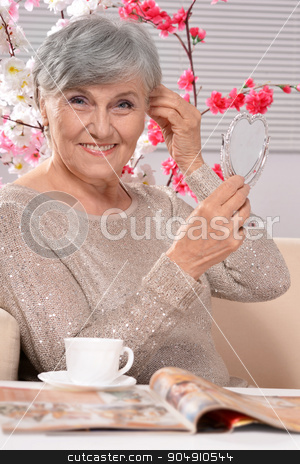 happy aged woman drinking coffee stock photo, Portrait of a happy aged woman drinking coffee by Ruslan Huzau