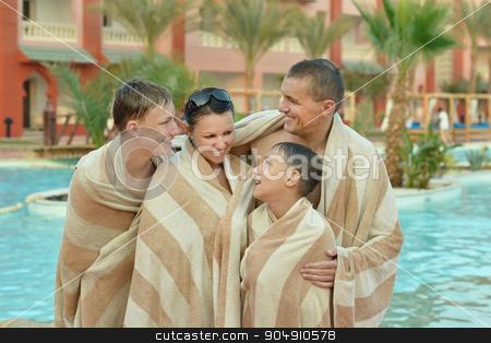 Happy family  near swimming pool stock photo, Happy family covered with towels near swimming pool by Ruslan Huzau