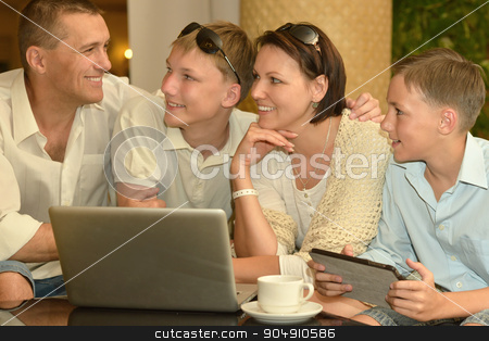 happy family  with laptop stock photo, happy family  with laptop at the table by Ruslan Huzau