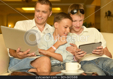 Father and sons with laptop stock photo, Father and sons with laptop at the table by Ruslan Huzau