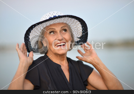 Elderly woman near lake stock photo, Portrait of a senior woman  in  summer near lake by Ruslan Huzau