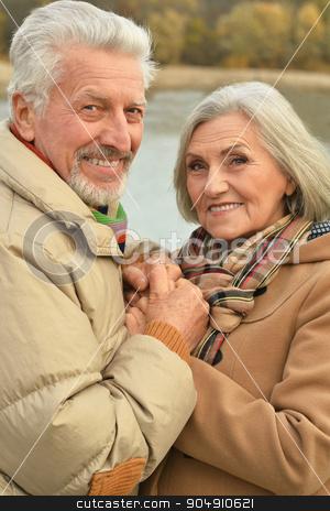 senior couple near river stock photo, Happy senior couple relax in autumn park near river by Ruslan Huzau