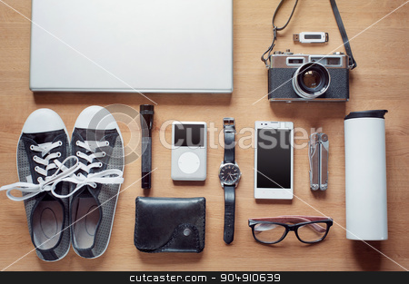 Overhead of essentials for modern young person stock photo, Outfit of modern traveler, student, woman or guy. Overhead of essentials on wooden background: camera, smart phone, glasses, flashlight, laptop, wallet, watch, gumshoes, thermos, multitool, mp3 player by Oleksii