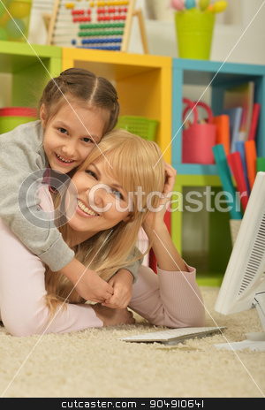 girl playing with mother on computer stock photo, Portrait of a little girl playing with mother on computer at home by Ruslan Huzau