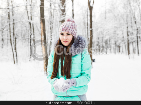 Young beautiful smiling girl holding snow in hands stock photo, Young beautiful smiling girl holding snow in hands by Satura86