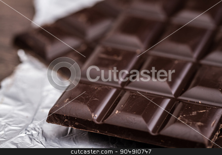 Dark Chocolate Bars on Foil and Wooden Table stock photo, Dark Chocolate bars on foil and brown wooden background by OZMedia