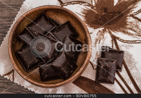 Roughly Cut Chunks of Chocolate Bars in Bowl stock photo, Roughly cut chunks of chocolate bars in a wooden bowl with napkin by OZMedia