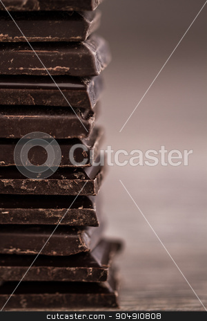 Chopped Dark Chocolate Bars Tower stock photo, Chopped dark chocolate bars aligned as a tower on brown wooden background by OZMedia