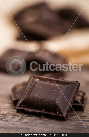 Dark Chocolate Bars on Crumbled Paper and Wooden Table stock photo, Dark Chocolate bars on crumbled paper and brown wooden background by OZMedia