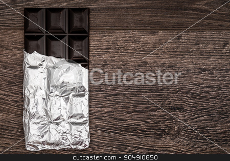 Dark Chocolate Bars on Foil and Wooden Table stock photo, Dark Chocolate bars on foil and brown wooden background with copy space by OZMedia