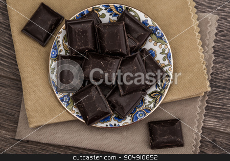 Dark Chocolate Bars on Napkins and Wooden Table stock photo, Dark Chocolate bars on napkins and brown wooden background by OZMedia