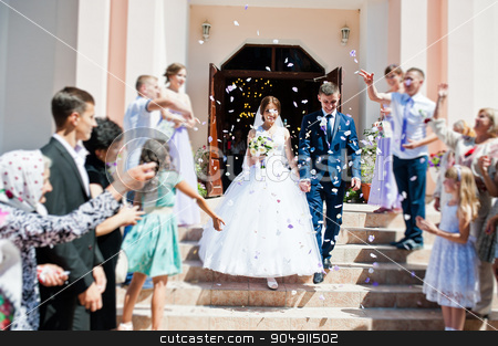 Guests sprinkled  rose petals  for newlywed after church registr stock photo, Guests sprinkled  rose petals  for newlywed after church registration by Andrii Shevchuk