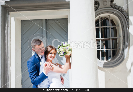 Wedding couple stay near antique window with column stock photo, Wedding couple stay near antique window with column by Andrii Shevchuk