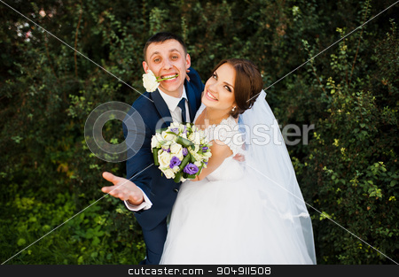 Funny bride with groom at rose on his mouth stock photo, Funny bride with groom at rose on his mouth by Andrii Shevchuk