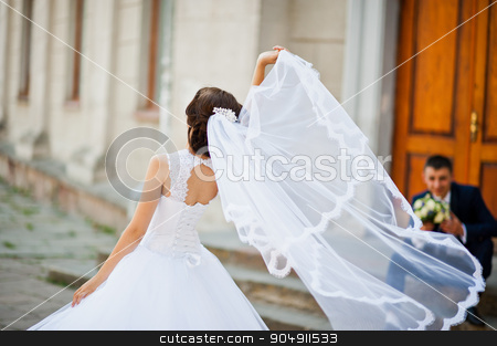 Bride play with veil  background her groom stock photo, Bride play with veil  background her groom by Andrii Shevchuk