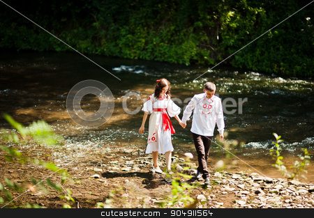 Love story of loving couple in national Ukraine dress. Near the  stock photo, Love story of loving couple in national Ukraine dress. Near the mountain river by Andrii Shevchuk