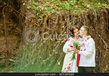 Love story of loving couple in national Ukraine dress. On the wo stock photo, Love story of loving couple in national Ukraine dress. On the wood with rocks by Andrii Shevchuk