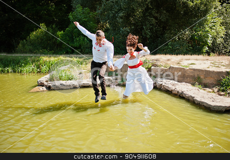 Love story of loving couple in national Ukraine dress. Jumpimg o stock photo, Love story of loving couple in national Ukraine dress. Jumpimg on the river by Andrii Shevchuk