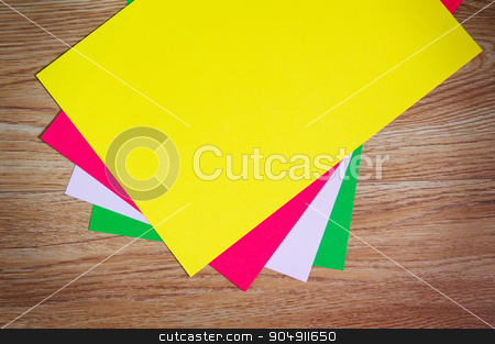 colored sheets of paper stacked on a wooden floor stock photo, colored sheets of paper stacked on a wooden floor. by timonko