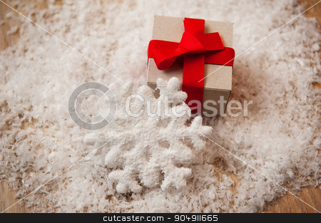 Christmas gift kraft paper and a snowflake in the snow stock photo, Christmas gift kraft paper and a snowflake in the snow. by timonko