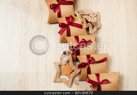 Handmade Christmas gifts from kraft paper and wooden toys on the Christmas tree stock photo, Handmade Christmas gifts from kraft paper and wooden toys on the Christmas tree. by timonko