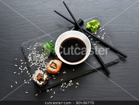 Rolls with sauce and chopsticks stock photo, Rolls with sauce and chopsticks on a slate table by Givaga