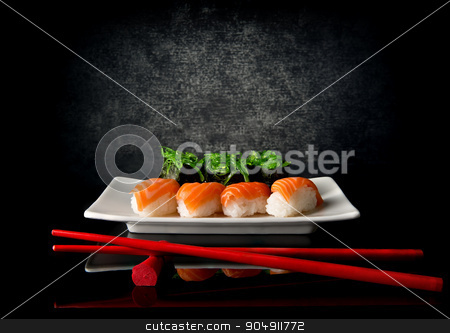 Sushi with chopsticks stock photo, Sushi on plate with red chopsticks on black background by Givaga