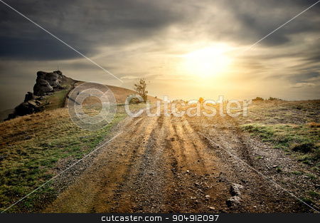 Stony road in mountains stock photo, Stony road in mountains at the sunset by Givaga