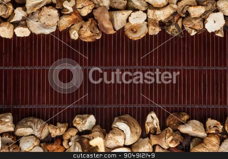 Dried mushroom on a dark  bamboo mat stock photo, Dried mushroom on a dark  bamboo mat, with space for text by alekleks