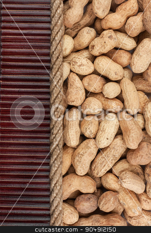 Peanut  lying on dark bamboo mat, for menu stock photo, Peanut  lying on dark bamboo mat, for menu, can be used as background by alekleks
