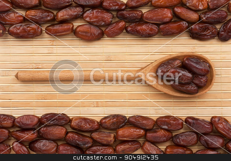 Wooden spoon with  dried  date  stock photo, Wooden spoon with  dried  date  lying on bamboo  mat by alekleks