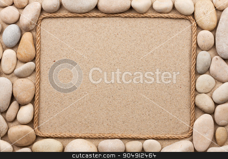 Frame made of rope lying on the sand among the white stones stock photo, Frame made of rope lying on the sand among the white stones, as background  by alekleks