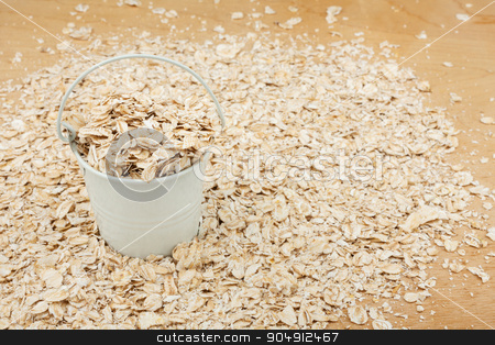White bucket with oat flakes  on the wooden floor stock photo, White bucket with oat flakes  on the wooden floor, as a background by alekleks