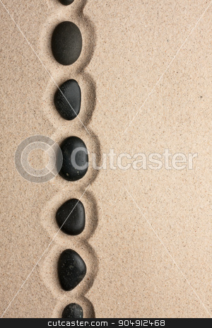 Line of black stones lying on the sand stock photo, Line of black stones lying on the sand, with space for your text by alekleks