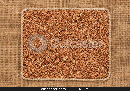 Frame made of rope with  buckwheat  grains on sackcloth stock photo, Frame made of rope with  buckwheat  grains on sackcloth, as background, texture by alekleks